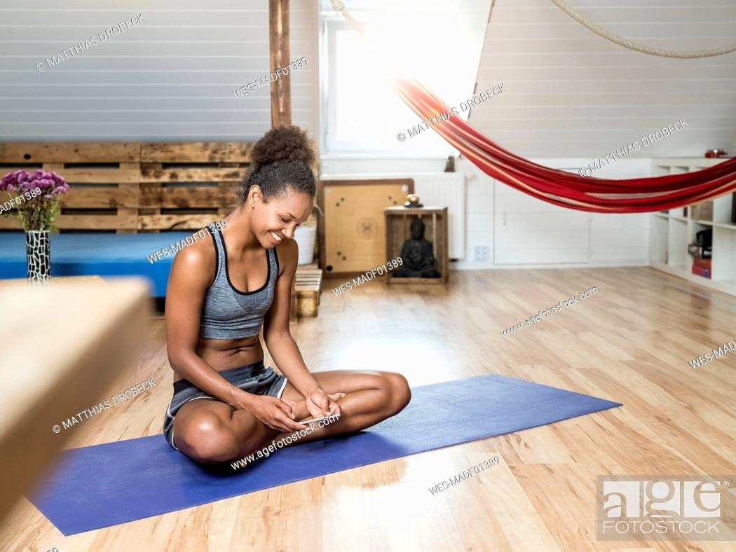 Stock Photo: Smiling young woman sitting on yoga mat looking at cell phone.