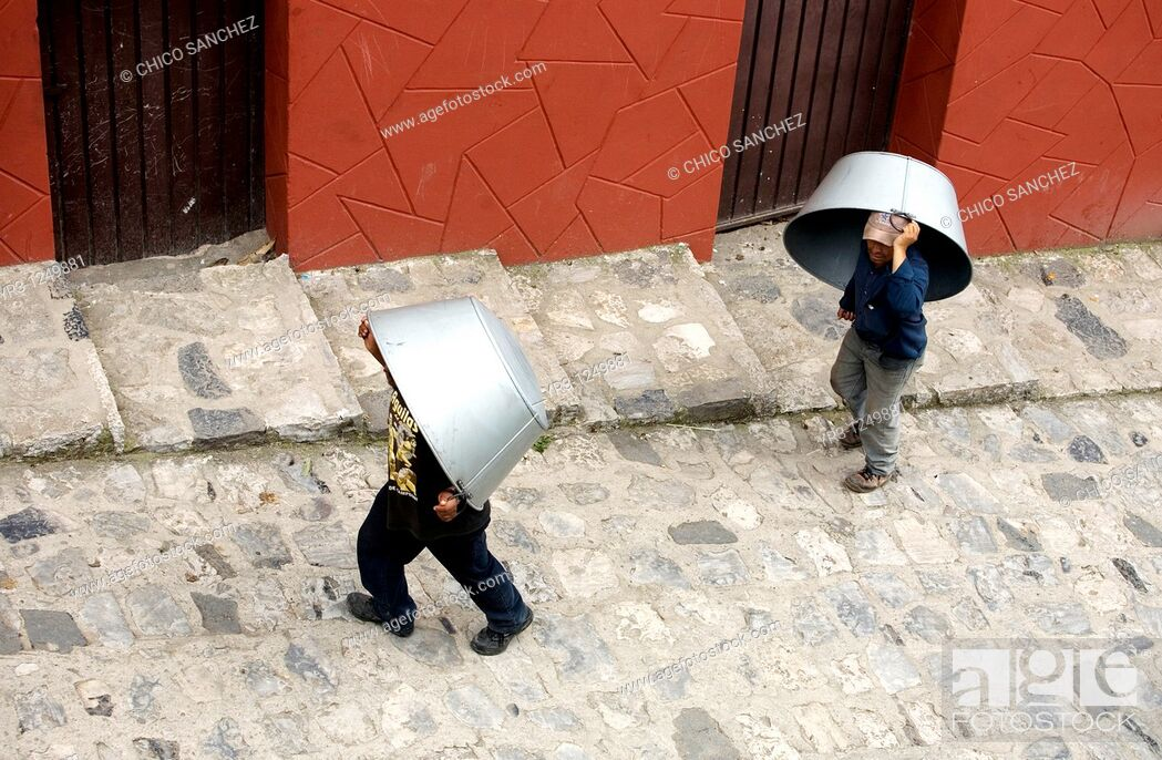 Stock Photo: Men carry large metal pans for sale or barter in the Sunday market in Cuetzalan del Progreso, Mexico. Cuetzalan is a small picturesque market town nestled in.