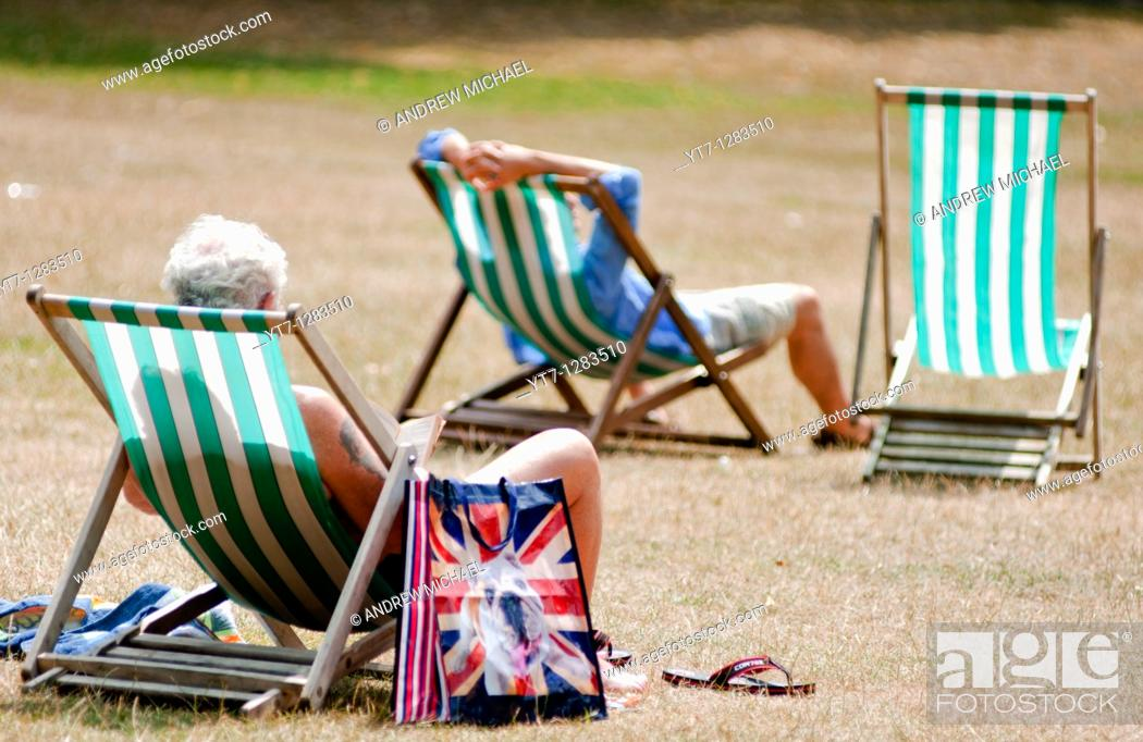 Stock Photo: Visitors relax in the summer on deck chairs, St James park, London, UK.