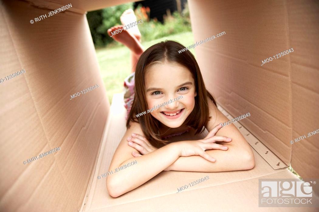 Stock Photo: Girl in backyard lying in cardboard box portrait.