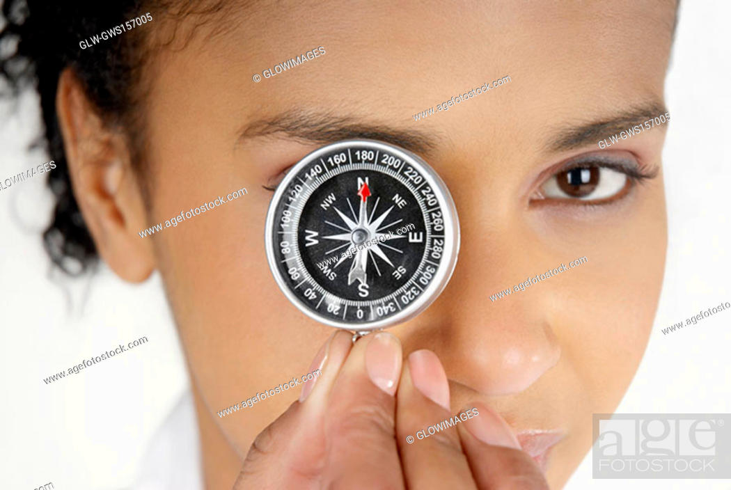 Stock Photo: Portrait of a businesswoman covering her eye with a compass.
