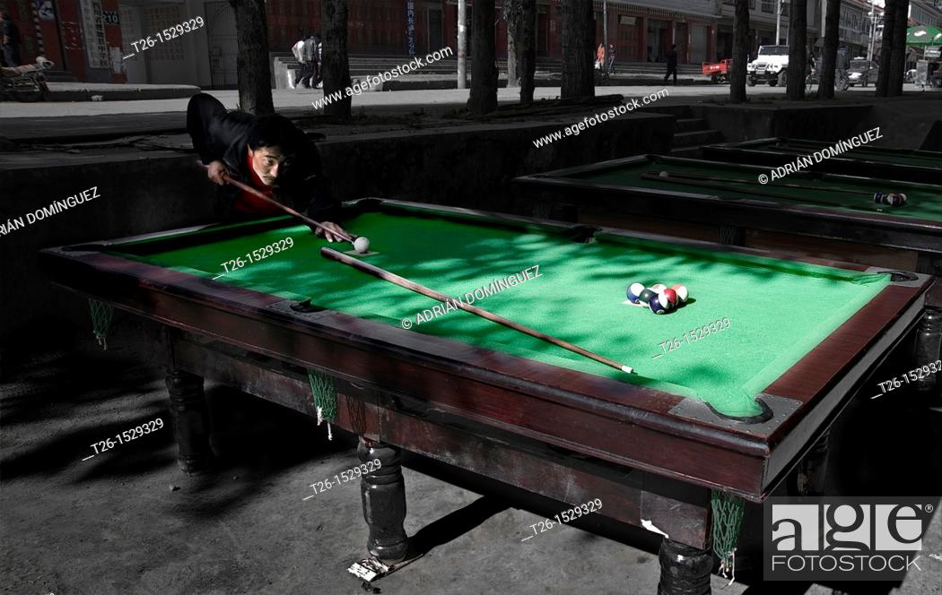 Stock Photo: Man playing pool in the street of Litang. China country.