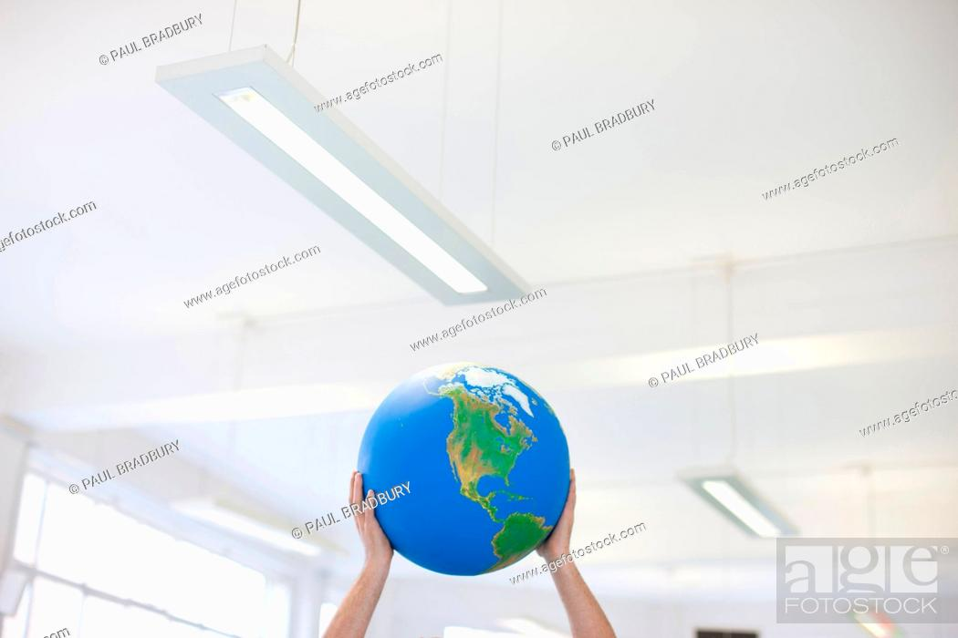 Stock Photo: Businessman lifting globe overhead in office.
