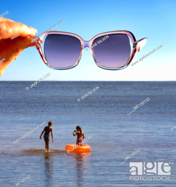 Stock Photo: Woman hand holding sunglasses in air over water. Kids in water with inflatable life ring.