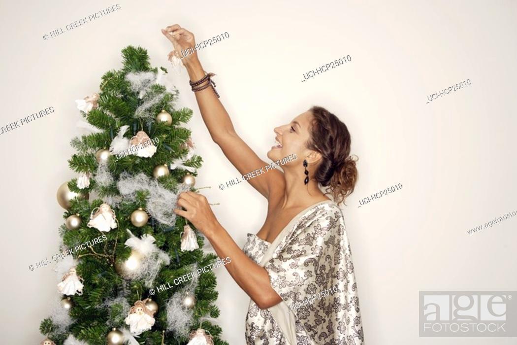 Stock Photo: Woman decorating Christmas tree.
