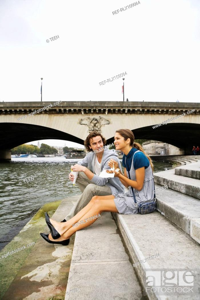 Stock Photo: Young couple sitting on steps by river Seine eating snack, Paris, France.