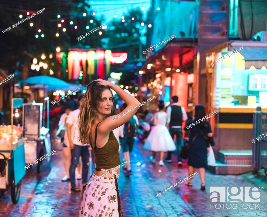 Imagen: Thailand, Bangkok, young woman in the city on the street at night.