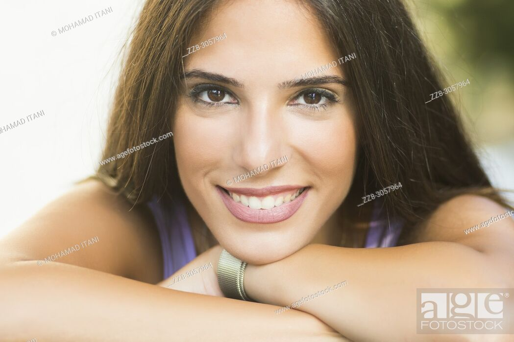 Stock Photo: Beautiful young woman smiling outdoors.