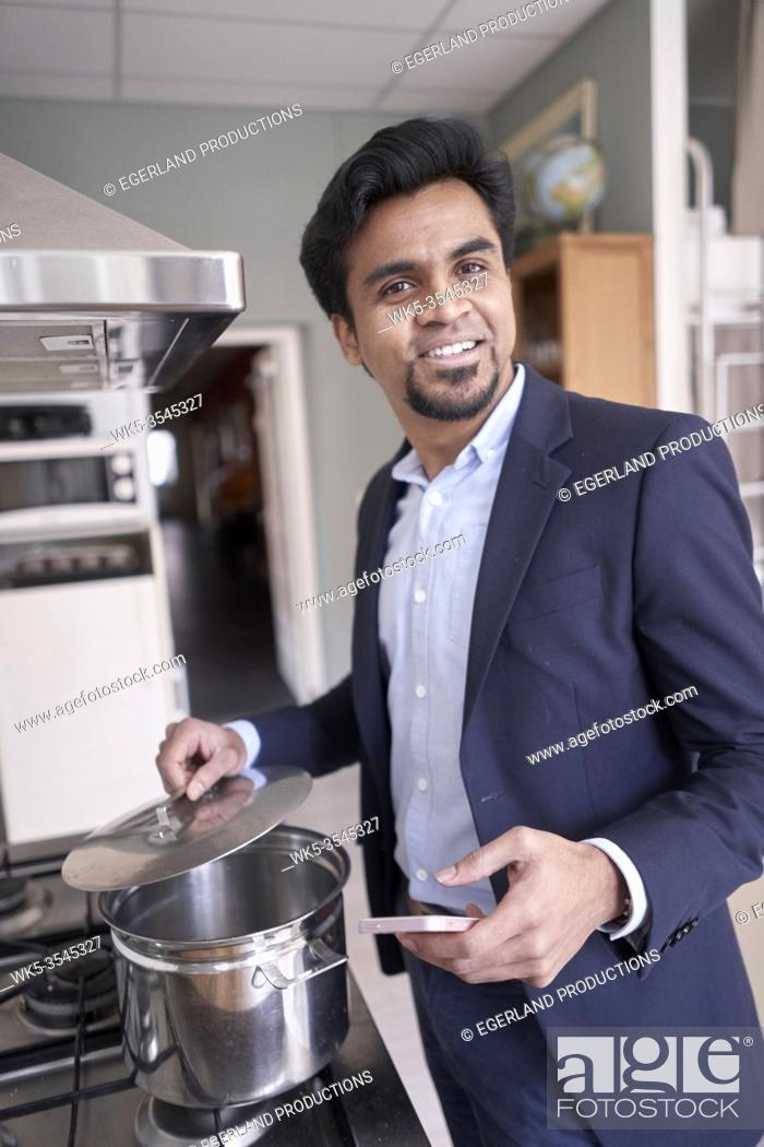 Stock Photo: Indian business man cooking with smartphone in hand.