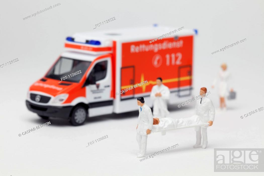 Stock Photo: Miniature paramedic figurines carrying a patient on a stretcher from a toy ambulance.