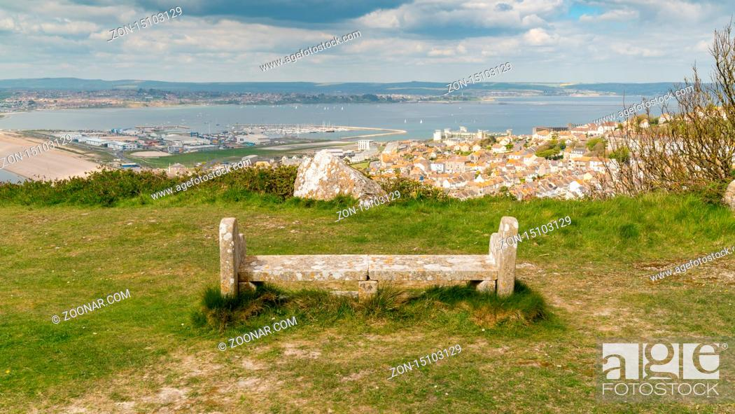 Stock Photo: A stone bench on the South West Coast Path with view towards Fortuneswell and Chesil Beach, Isle of Portland, Jurassic Coast, Dorset.