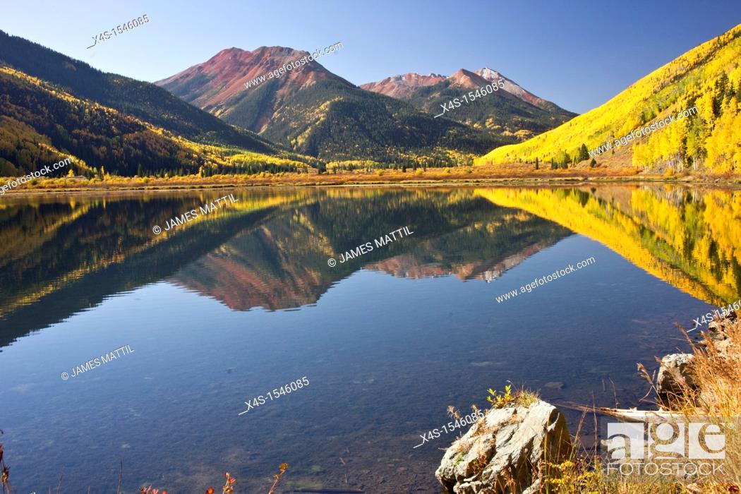 Stock Photo: Rocky Mountain foliage reflects in a clear mountain lake.