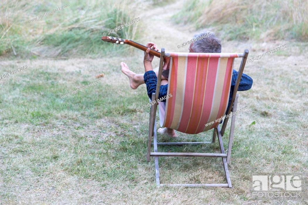 Imagen: Man sitting in chair and playing guitar.