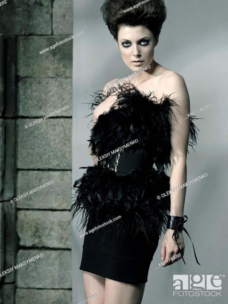 Stock Photo: High fashion photo of a beautiful woman wearing elegant black feathery dress.