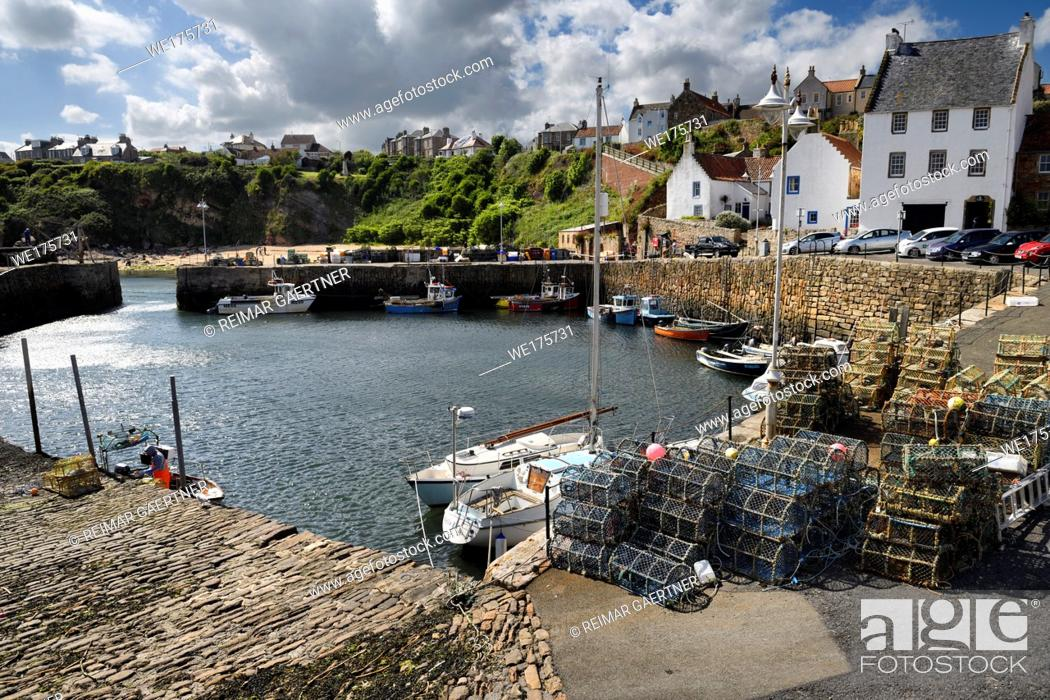 Stock Photo: Stone pier walls at Crail Harbour with fishing boats and lobster traps and cliff with beach at Crail Fife Scotland UK.