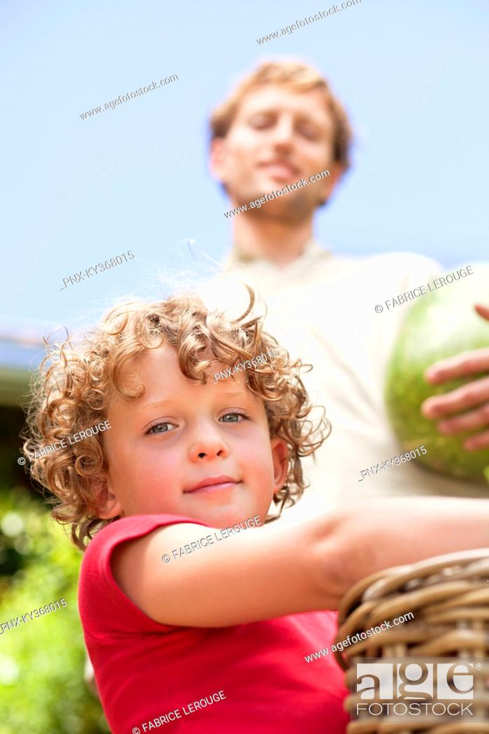 Stock Photo: Low angle view of father and son holding fruits.