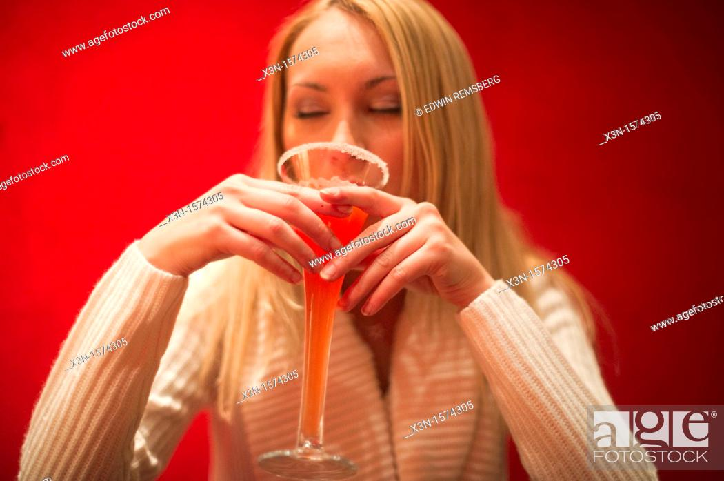 Stock Photo: Woman drinking red cocktail.