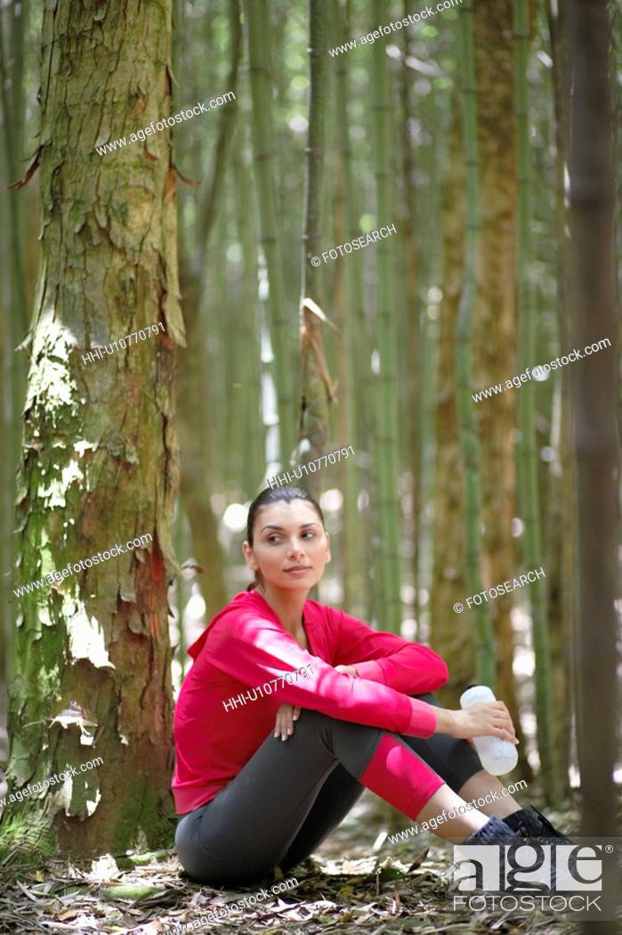Stock Photo: Young woman in sports clothing sitting in forest.