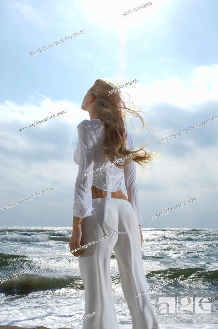 Stock Photo: Young woman looking at sky above ocean back view.