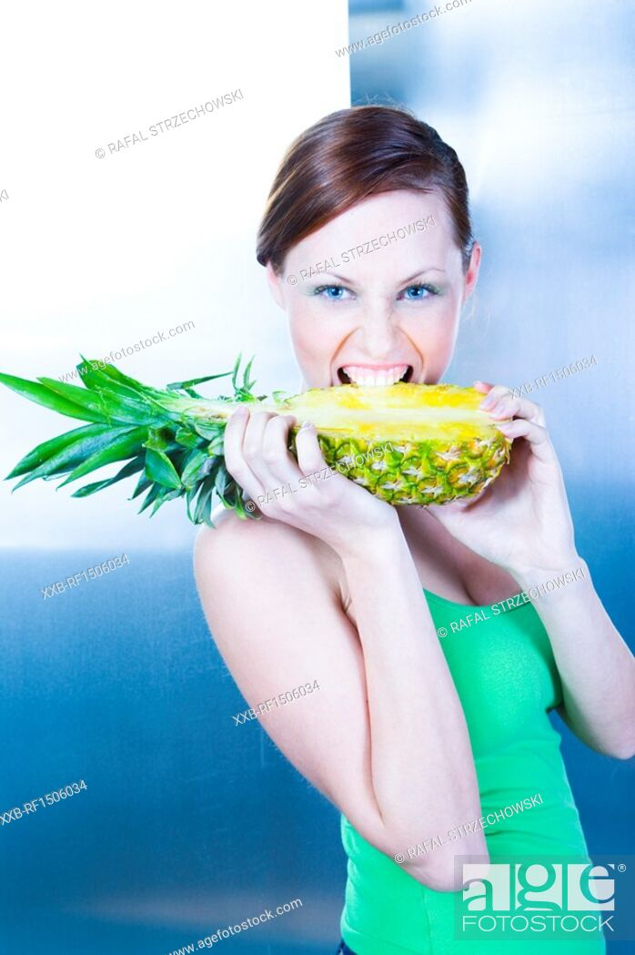 Stock Photo: young woman holding pineapple.