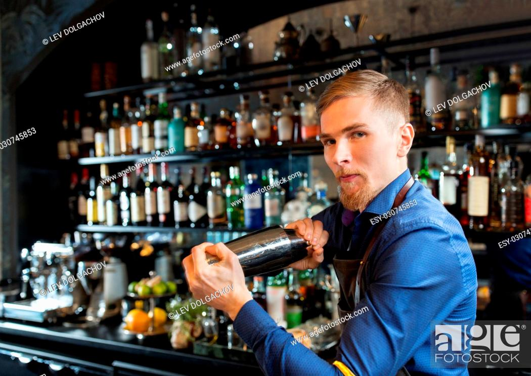Stock Photo: alcohol drinks, people and luxury concept - barman with shaker preparing cocktail at bar.