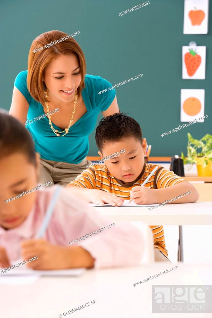 Stock Photo: Close-up of a schoolboy writing on a notebook with a pencil with his female teacher standing behind him.