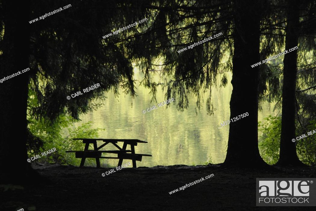Stock Photo: A picnic bench waits for revelers to enjoy an emerald-green lake.