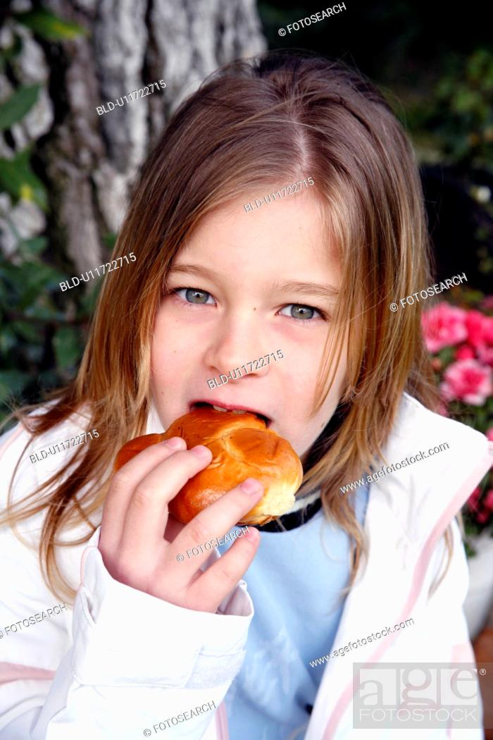 Stock Photo: Young girl eating a doughnut.