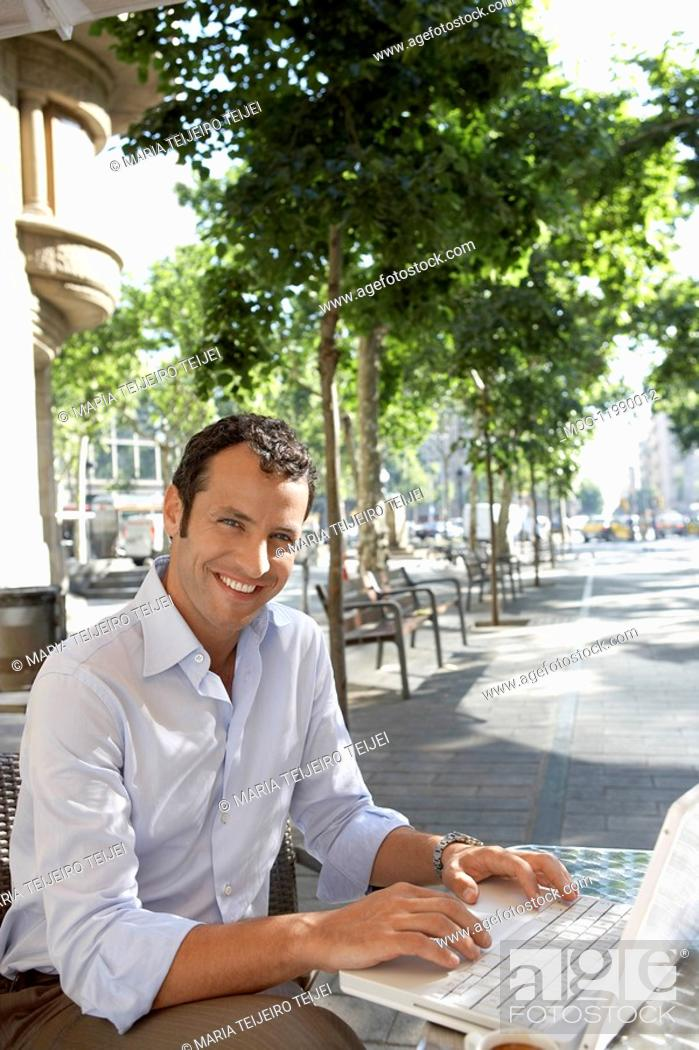 Stock Photo: Businessman using laptop at outdoor cafe.