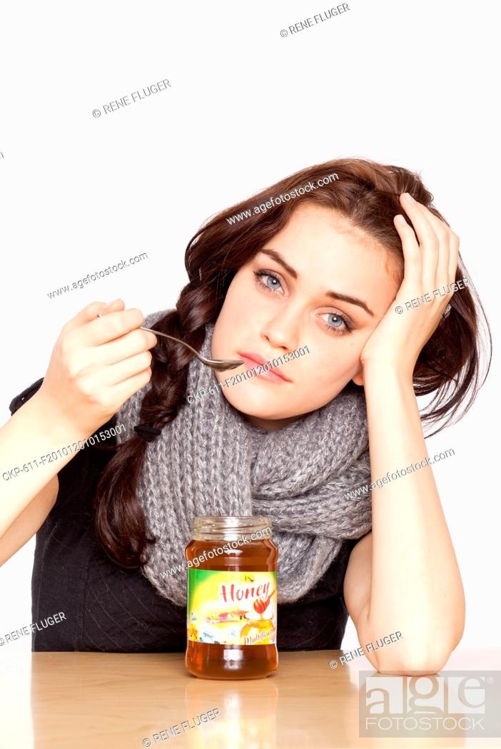 Stock Photo: A beautiful young woman, lady, girl, cold, runny nose, headache, tea, honey, spoon, scarf.