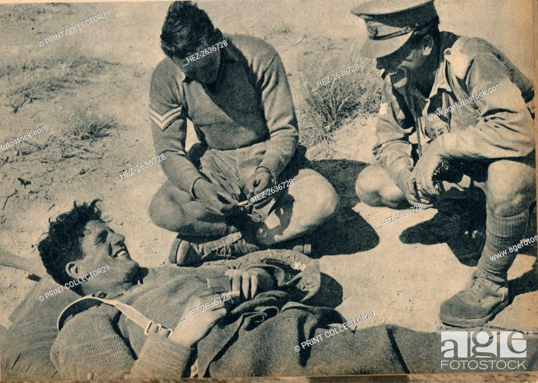 Stock Photo: 'Ambulance men with a wounded anti-tank gunner', c1942 (1944). Artist: Unknown.