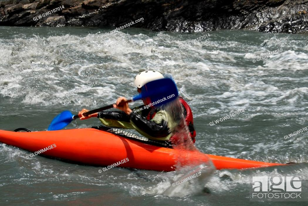 Stock Photo: Side profile of a person kayaking in a river.
