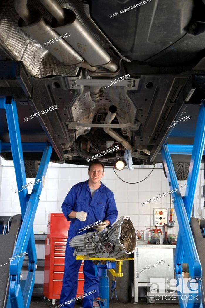 Stock Photo: Mechanic with clipboard and part by elevated car, portrait, low angle view.