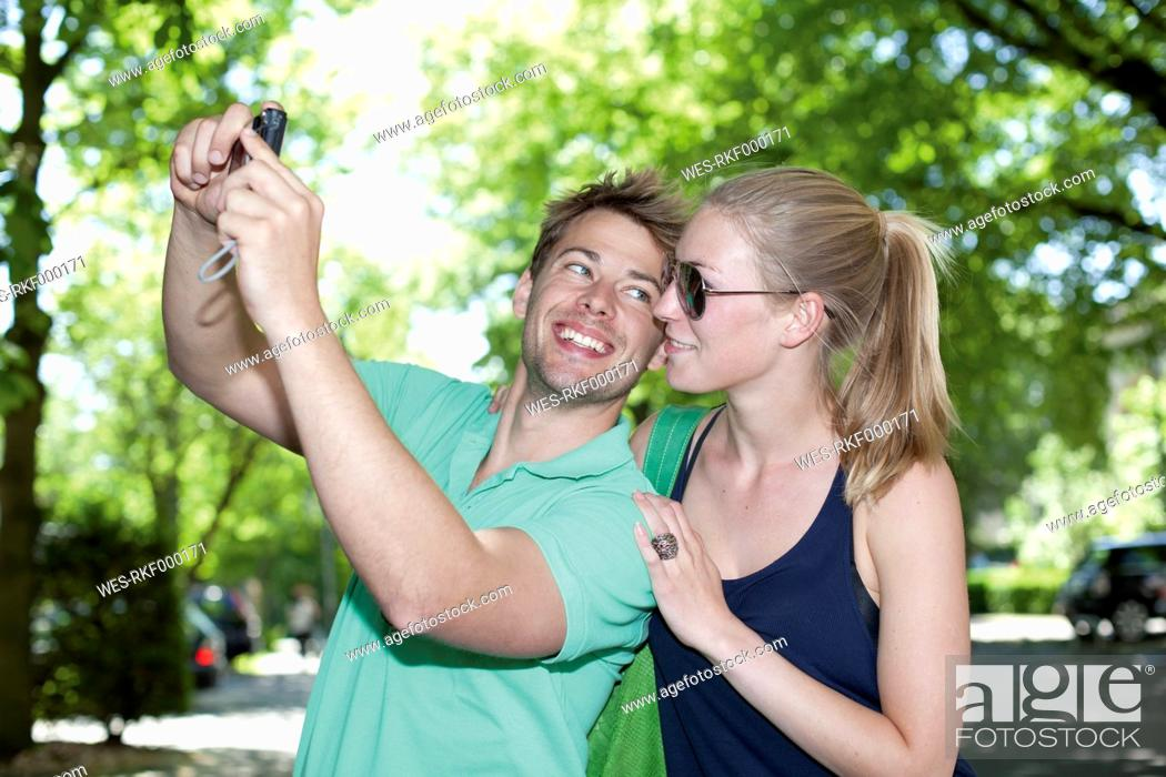 Stock Photo: Germany, North Rhine Westphalia, Duesseldorf, Couple taking photo of themselves, smiling.