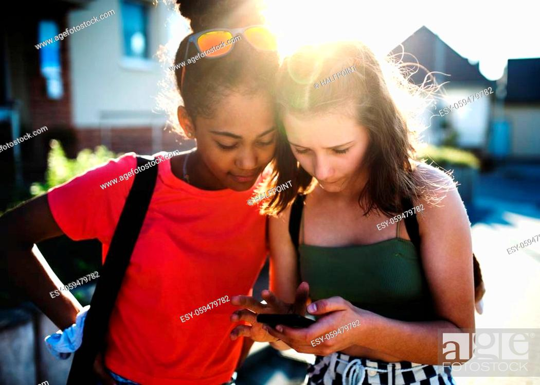 Stock Photo: Front view of teenager girls friends outdoors in city, using sartphone.