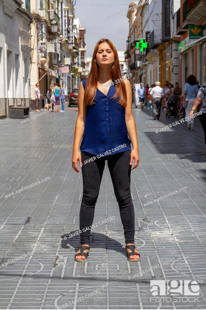 Stock Photo: Young woman posing challenging in the middle of the street.