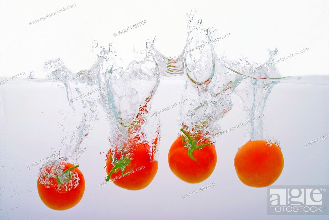 Stock Photo: Tomatoes thrown into water.