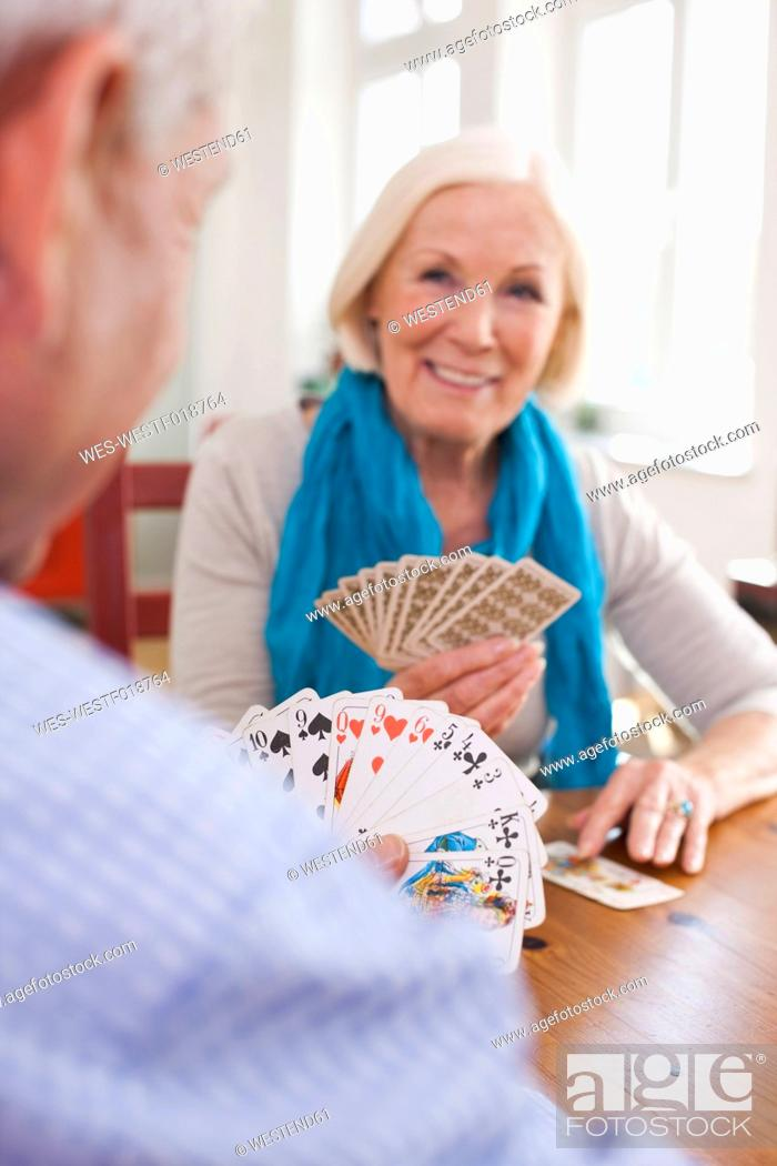 Stock Photo: Germany, Leipzig, Senior man and woman playing cards, smiling.