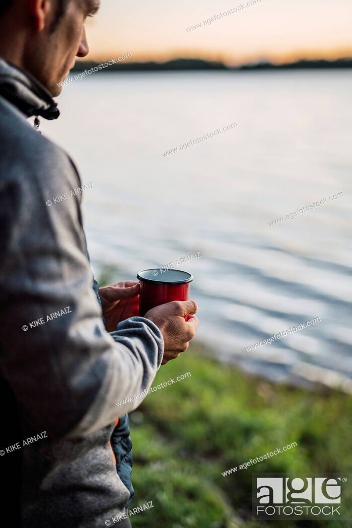 Stock Photo: Man looking at the lake, drinking coffee.