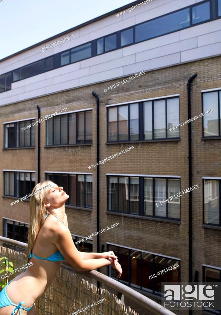 Stock Photo: Woman sunbathing on city balcony.