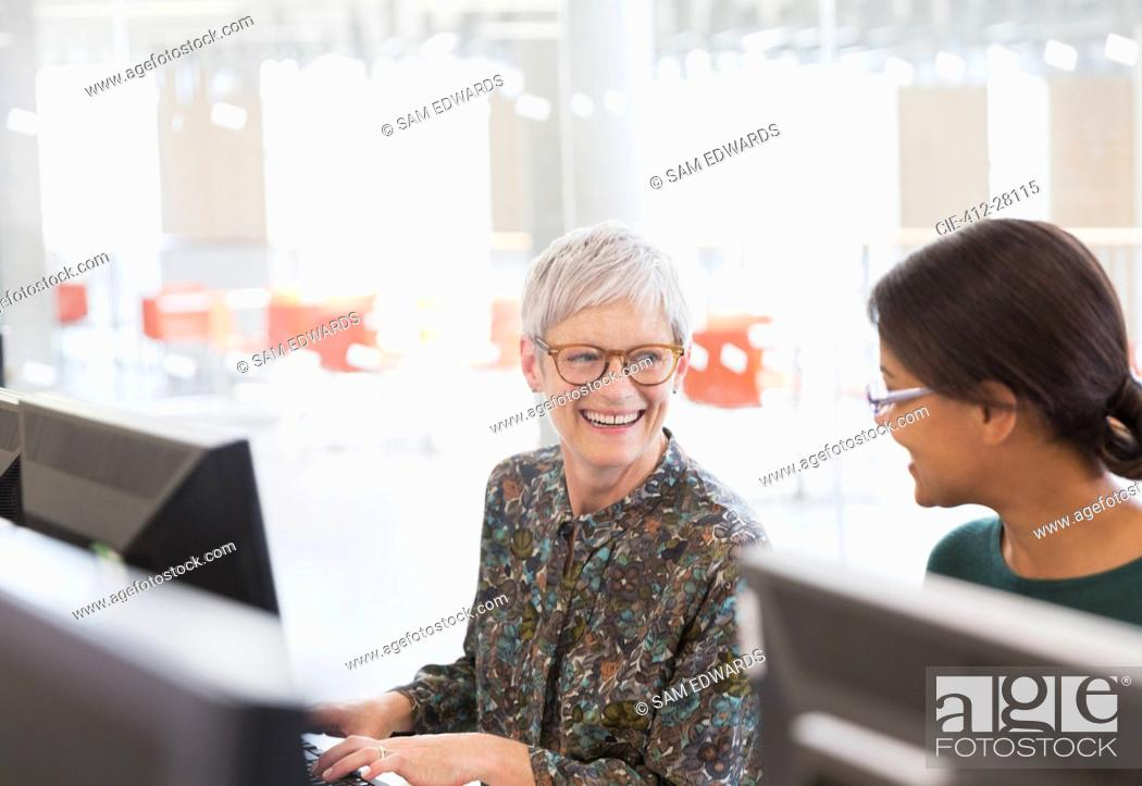 Stock Photo: Smiling women talking at computers in adult education classroom.