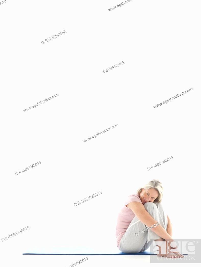 Stock Photo: Mature woman sitting on yoga mat.