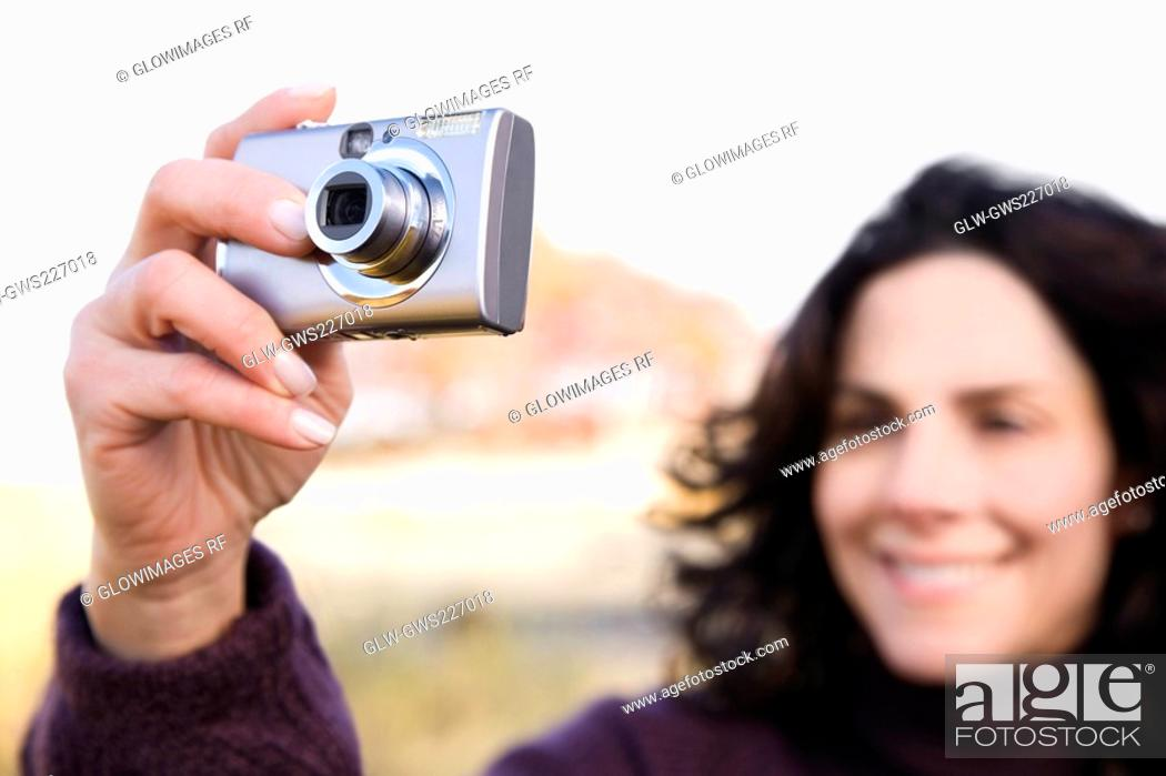 Stock Photo: Close-up of a mature woman photographing with a digital camera.
