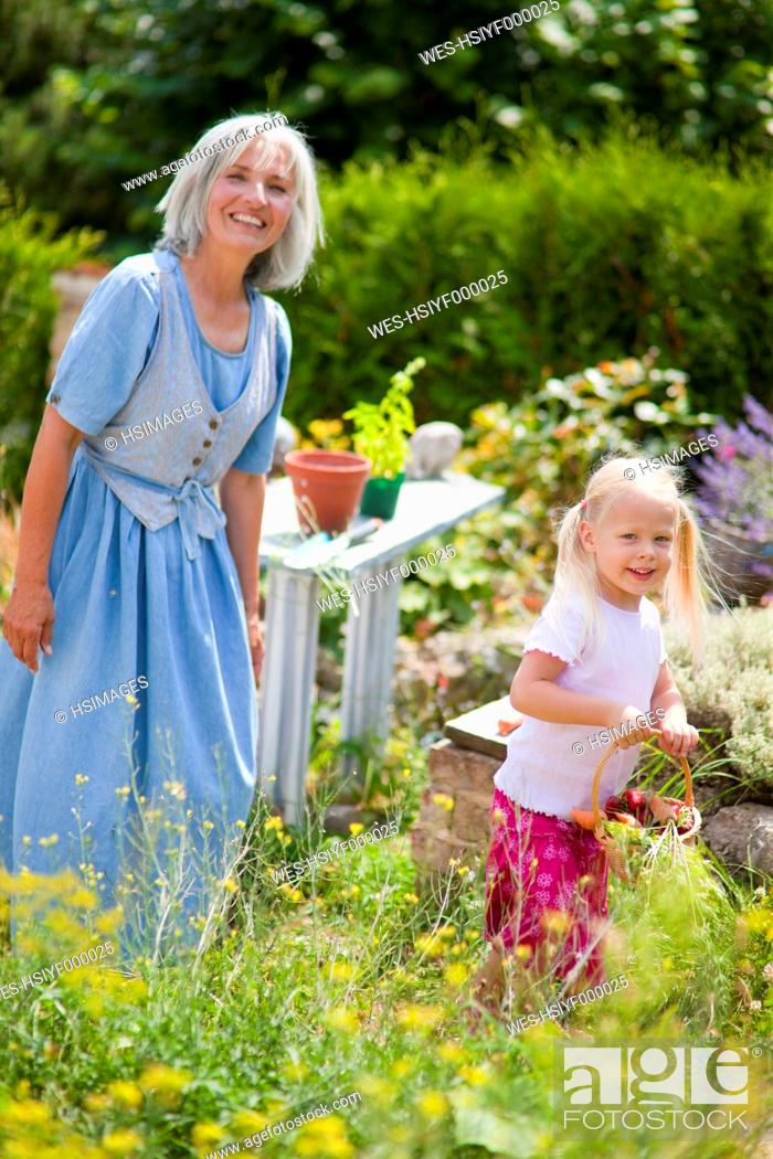 Stock Photo: Germany, Bavaria, Mature woman with girl in garden.