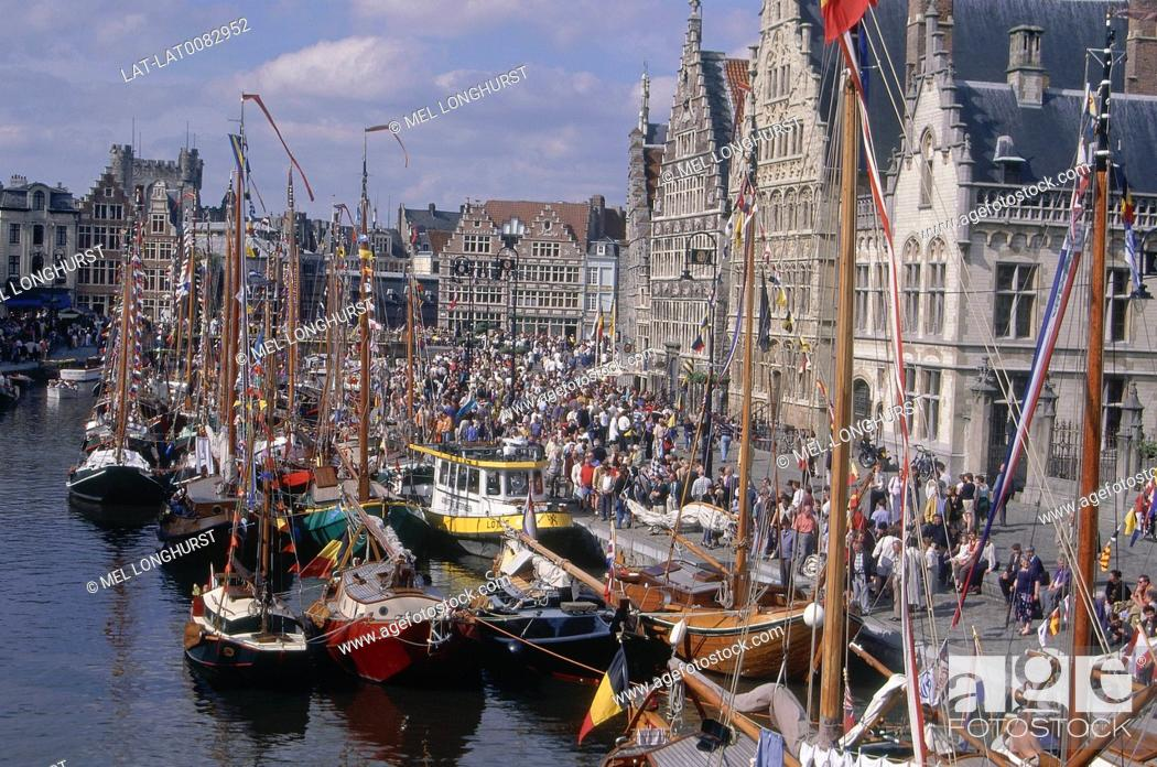 Stock Photo: Waterway. Yachts moored. Flags. Historical buildings on waterfront. Step gables.