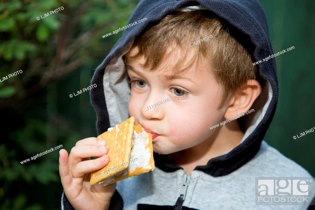 Stock Photo: Young boy trying to eat a sticky s'more outdoors; Edmonton, Alberta, Canada.
