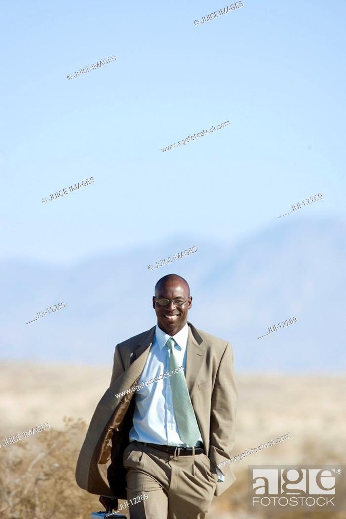 Stock Photo: Businessman walking in desert, smiling, portrait.