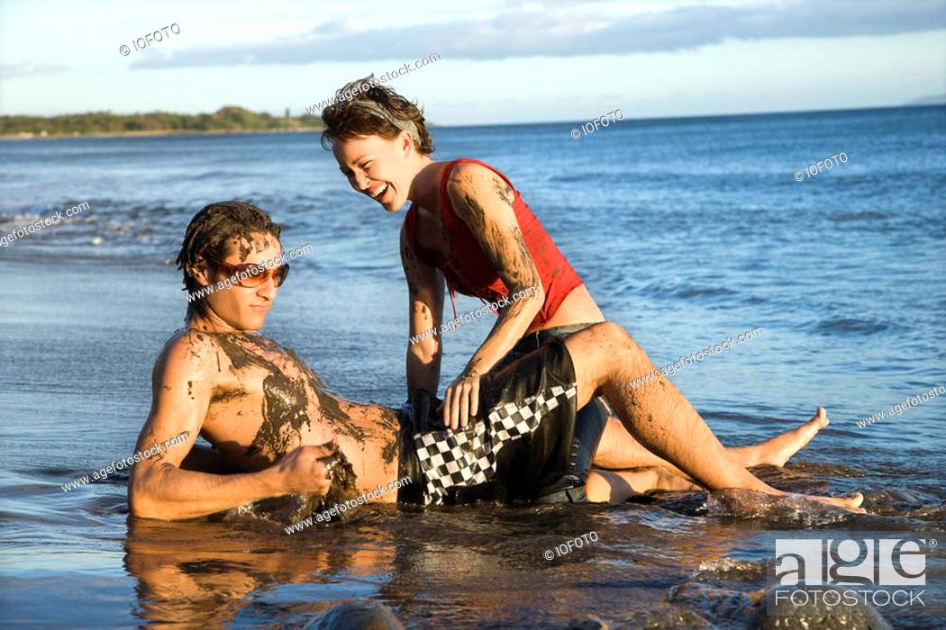 Stock Photo: Caucasian young adult couple frolicking on beach.