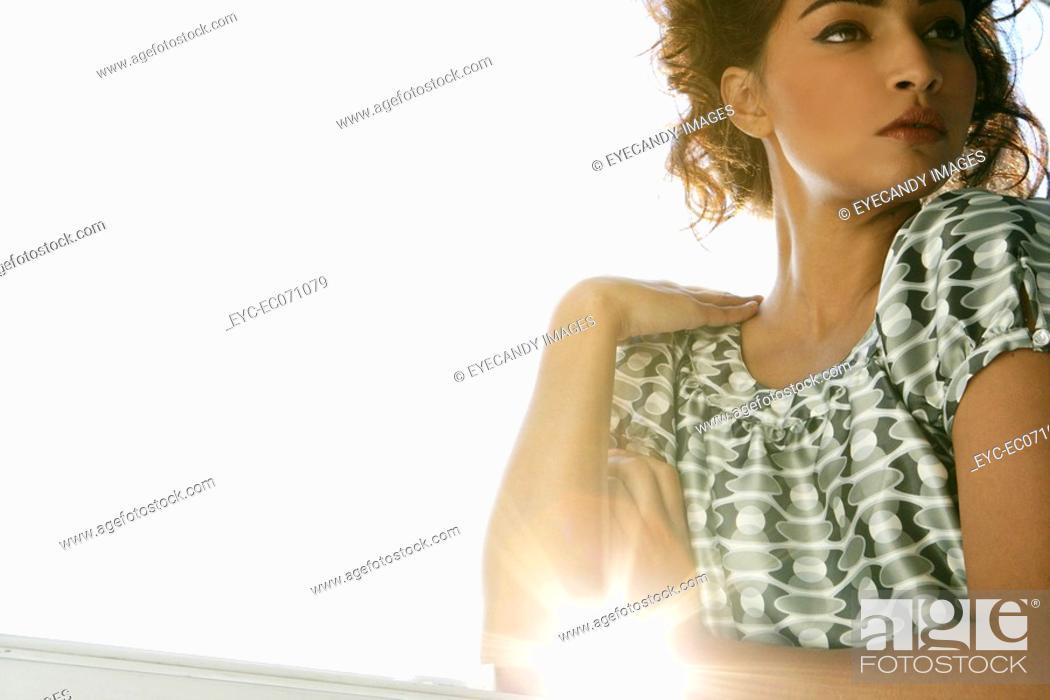Stock Photo: Young stylish woman standing near window.