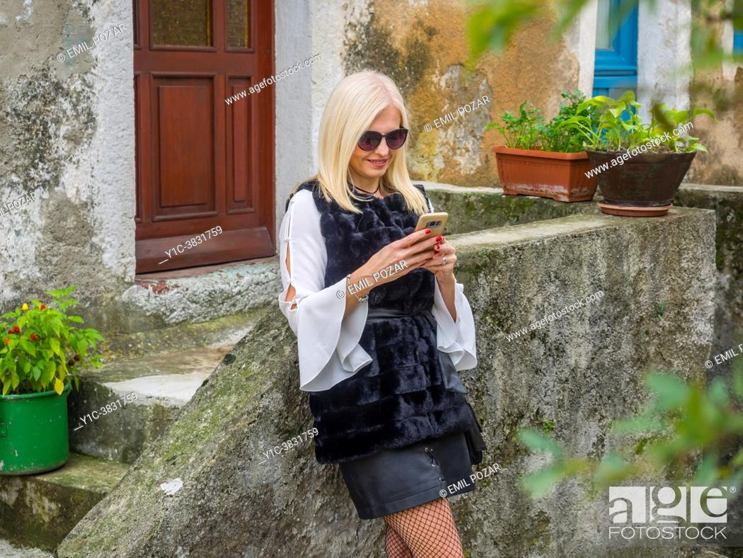 Stock Photo: Attractive mature blonde woman is checking e-mail on smartphone.